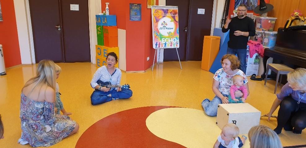 dzieci na zajęciach pt. Gordonki, prowadząca gra i śpiewa na gitarze