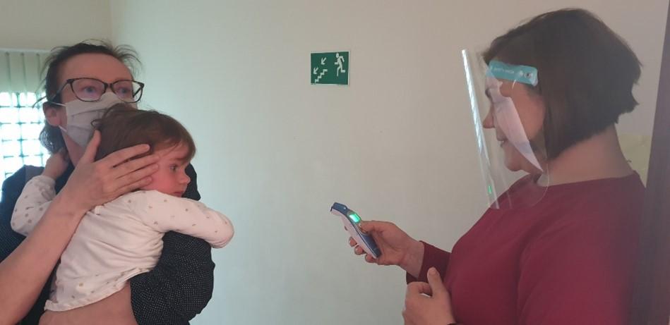 Pracownik Fundacji mierzy temperaturę przybyłej matki z dzieckiem